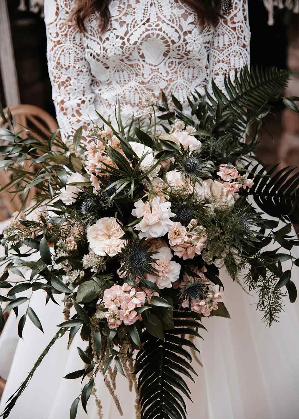 Der Brautstrauß besteht aus locker zusammengesteckten Wildblumen in Rosatönen und grünen Akzenten.