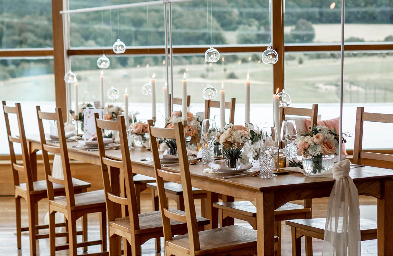 hübsch eingedeckte Hochzeitstafel mit dekorativen Tischgestell an dem kleine runde Windlichter herunterhängen