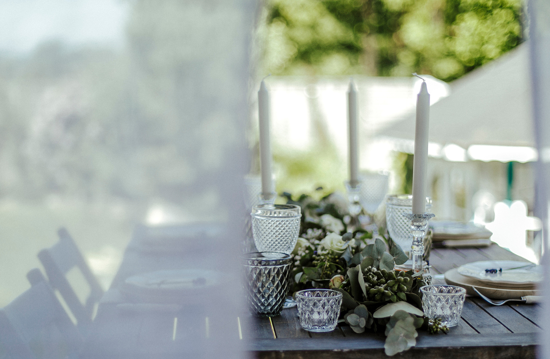 Hochzeitstafel ist nachhaltig dekoriert mit Blättern aus dem Garten und wiederverwendbaren Gläsern.