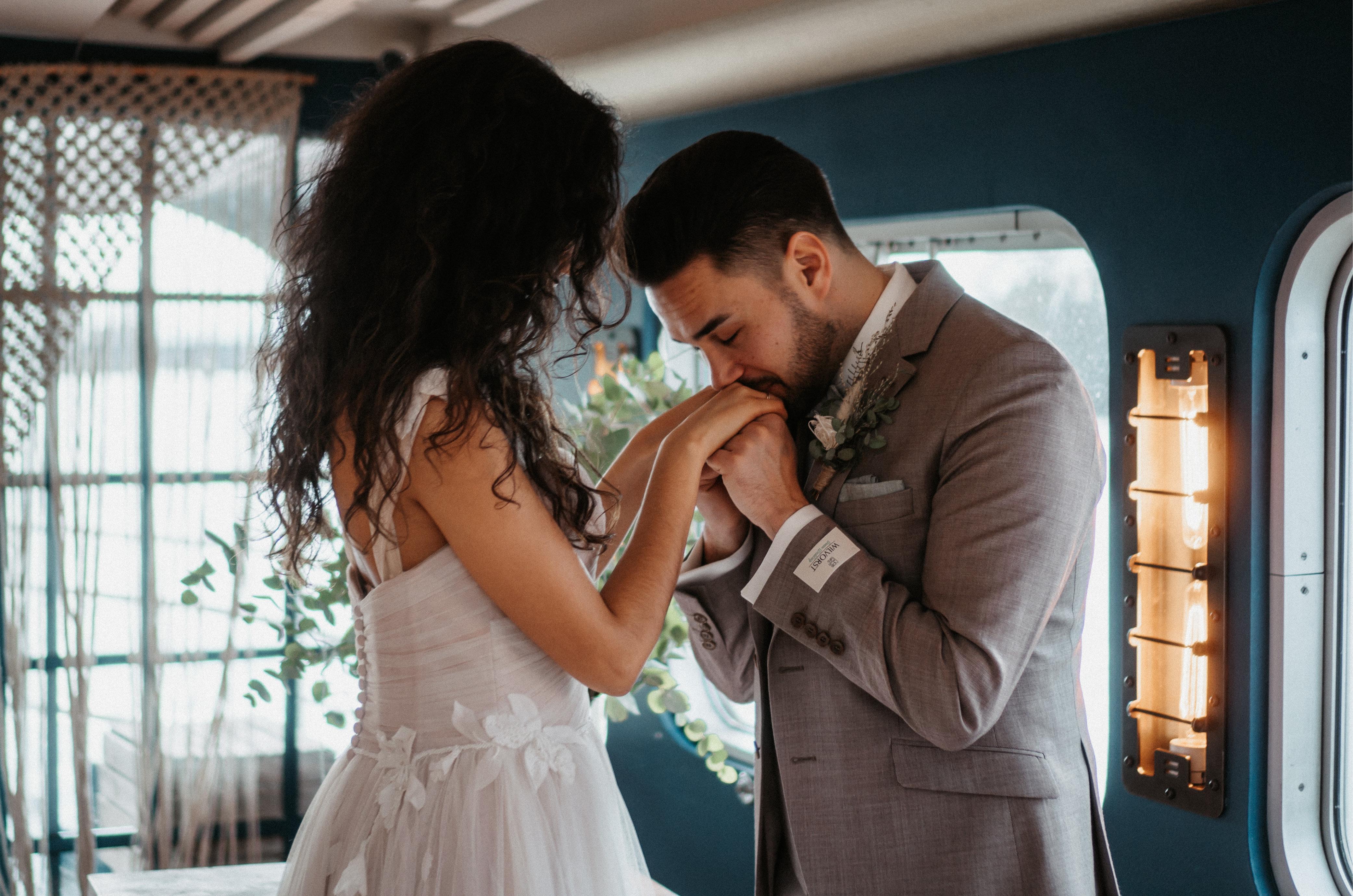 Bräutigam küsst Braut auf die Hände nach der freien Trauung.