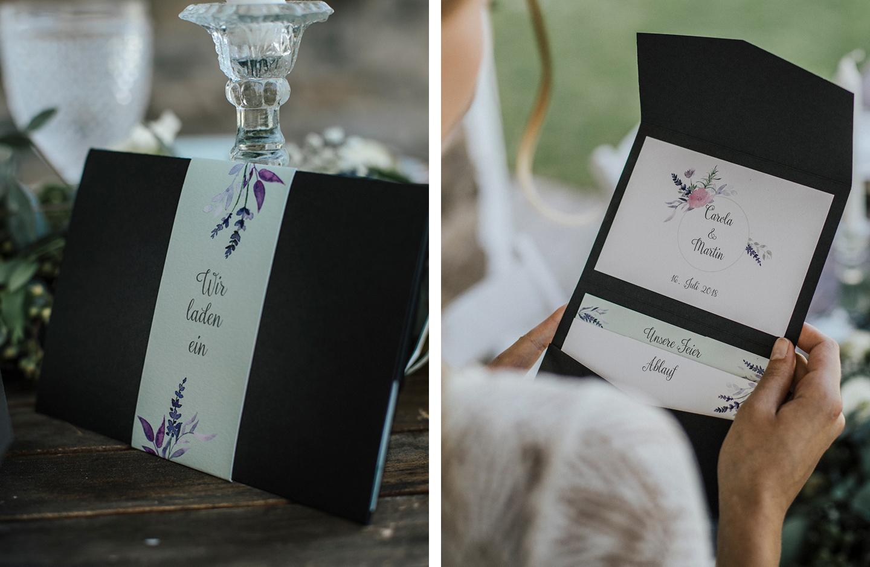 Braut hält schwarze Hochzeitseinladung mit liebevollen Illustrationen von Lavendel in der Hand.