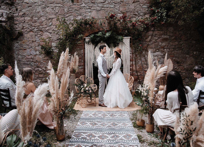 Checkliste Hochzeitsdeko: Die freie Trauung findet mit Teppichen, Makramee-Trauubogen und Pampasgras statt.