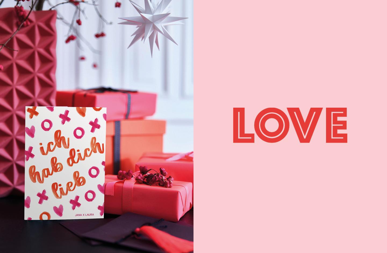 Valentinstag Geschenke: Ich hab dich lieb Karte in Orange & Pink steht auf einem mit Geschenken dekorierten Tisch.