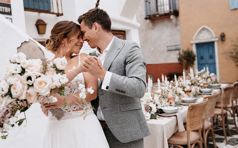 Braut und Bräutigam sehen sich tief in die Augen und strahlen über das ganze Gesicht. Der Blumenstrauß der Braut in hellen Tönen wird von ihr in der Hand gehalten. Im Hintergrund ist der Hochzeitstisch zur mediterranen Hochzeit zu sehen.