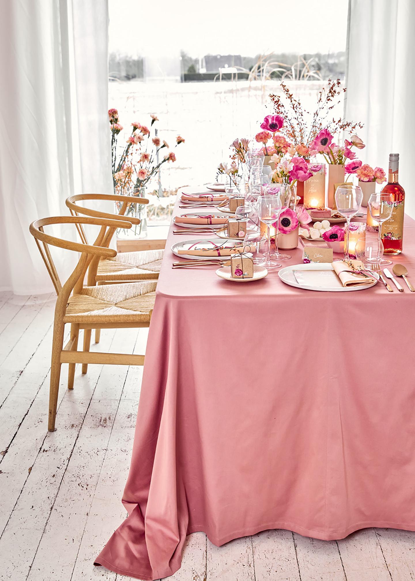 Tischdeko Hochzeit: Hochzeitstisch in vielen Pinktönen, mit geflochtenen hellbraunen Stühlen in einer weißen Vintage-Location.