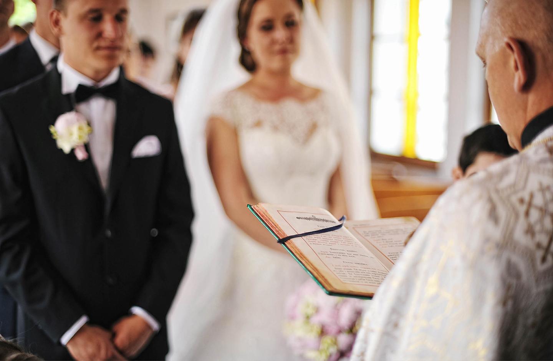 Priester liest aus der Bibel vor. Vor im steht das Hochzeitspaar.