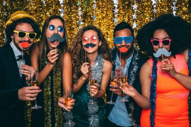 Freunde feiern zusammen und machen lustige Bilder mit verschiedenen Accessoires.