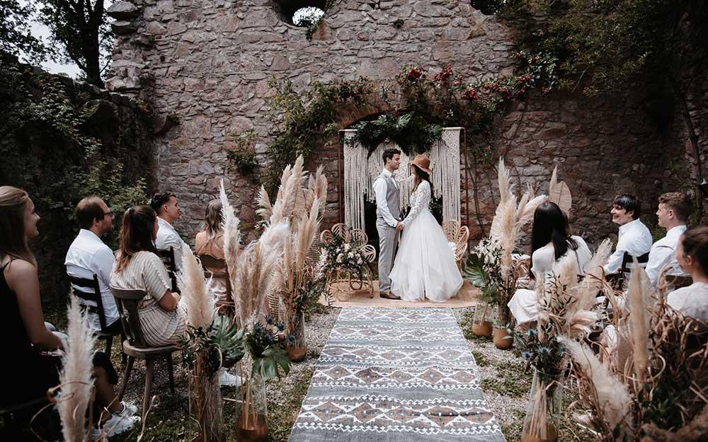 Die Freie Trauung findet unter freiem Himmel vor einer wunderschönen alten Steinwand statt- Die Deko ist im Boho-Greenery Stil gehalten und enthält viele Trockenblumen, Pampasgras und Elemente in Beige und Naturtönen. Die Gäste warten gespannt.