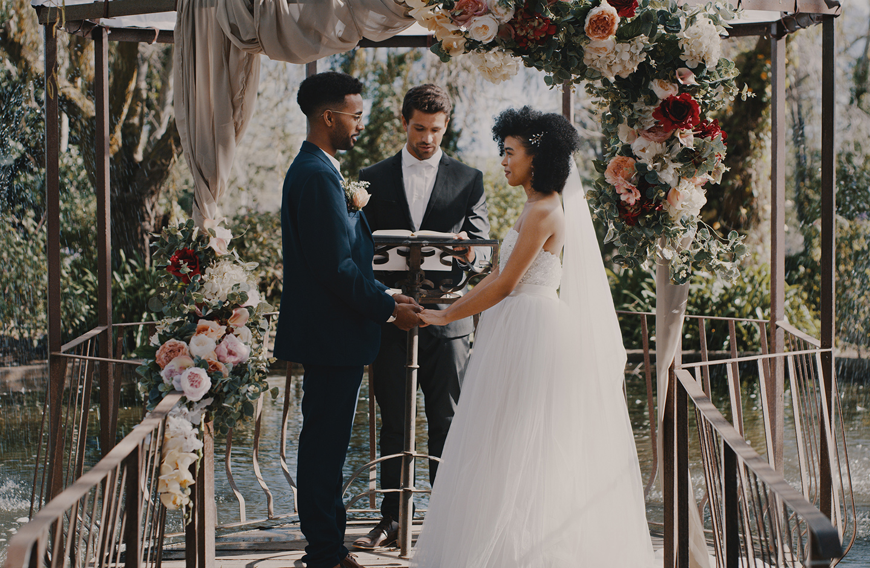Verliebtes Brautpaar steht vor aufwendigen Traubogen & gibt sich bei einer Tiny Wedding im Freien das Ja Wort.