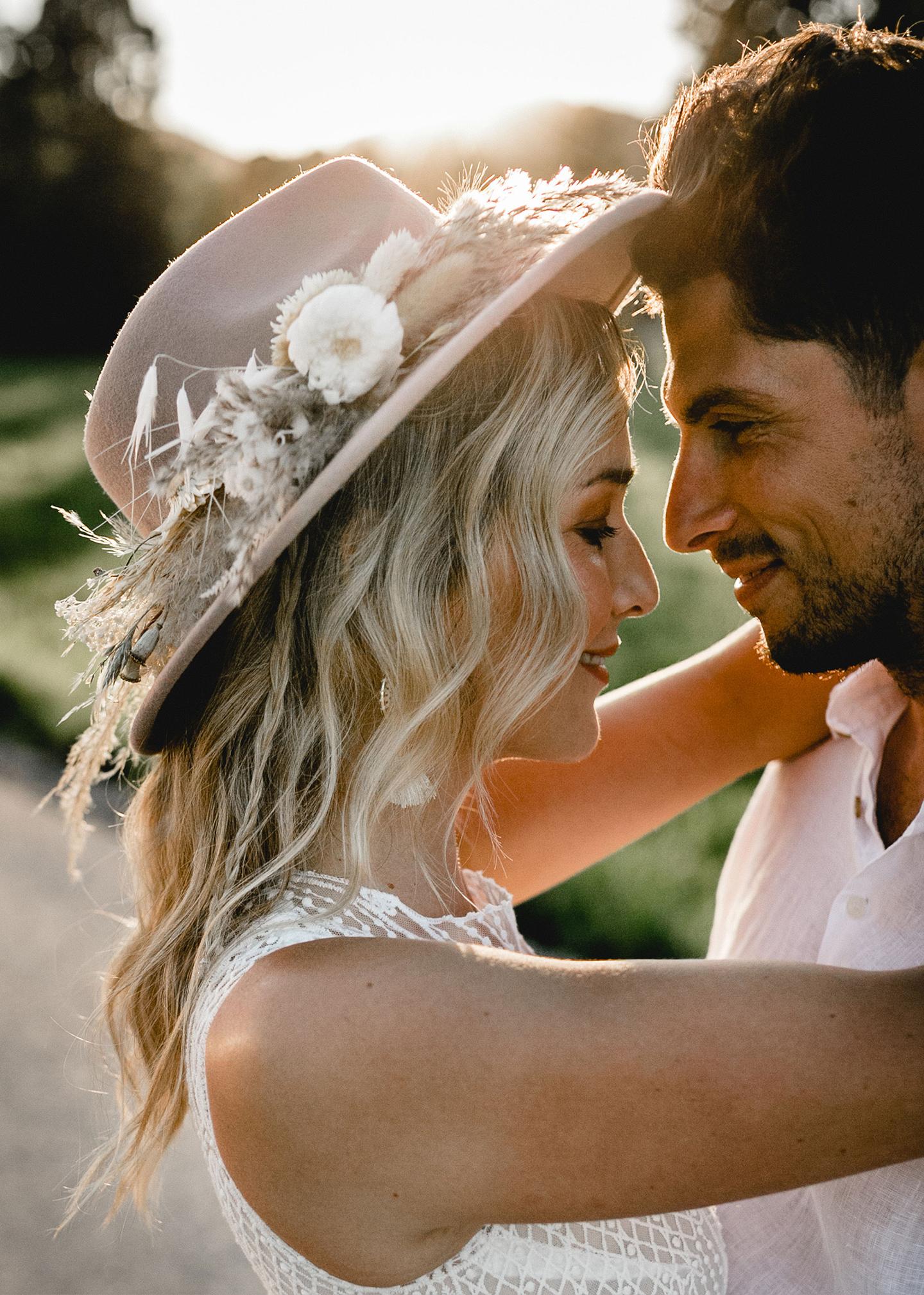 Verliebt umarmt sich das Brautpaar im untergehenden Sonnenlicht.