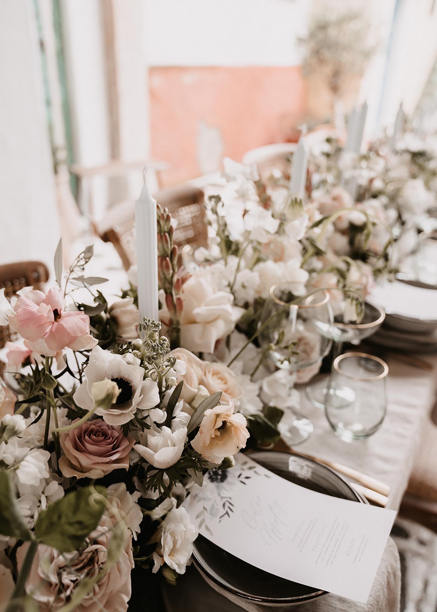 Der Hochzeitstisch mit Blumen geschmückt und mit den gedeckten Plätzen ist zu sehen. Die Blumen stechen durch ihre Vielfalt und unterschiedlichen Farben hervor.