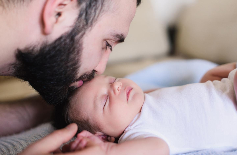 Vater küsst Baby auf den Kopf
