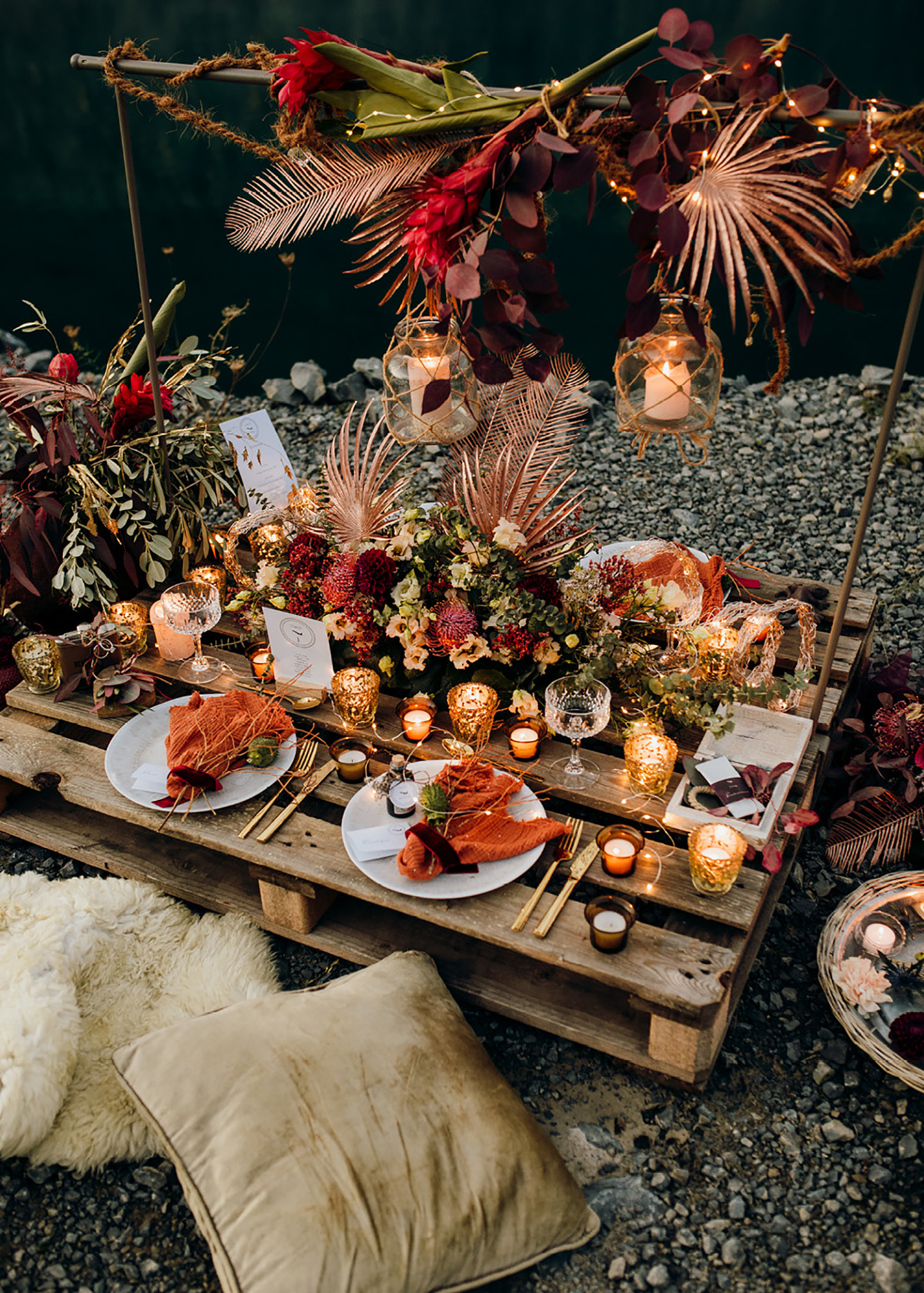 Die Hochzeitstafel aus einer Holzpalette, mit warmen Farbakzenten geschmückt vor dem Wasser im Steinbruch