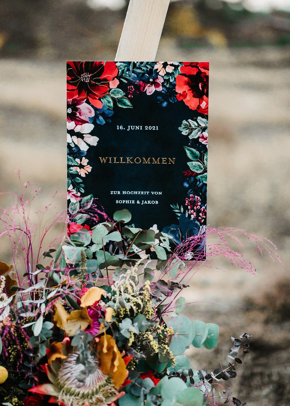 Willkommensschild in dunkelblau mit bunten, handgezeichneten Blüten und goldener Schrift-Veredelung