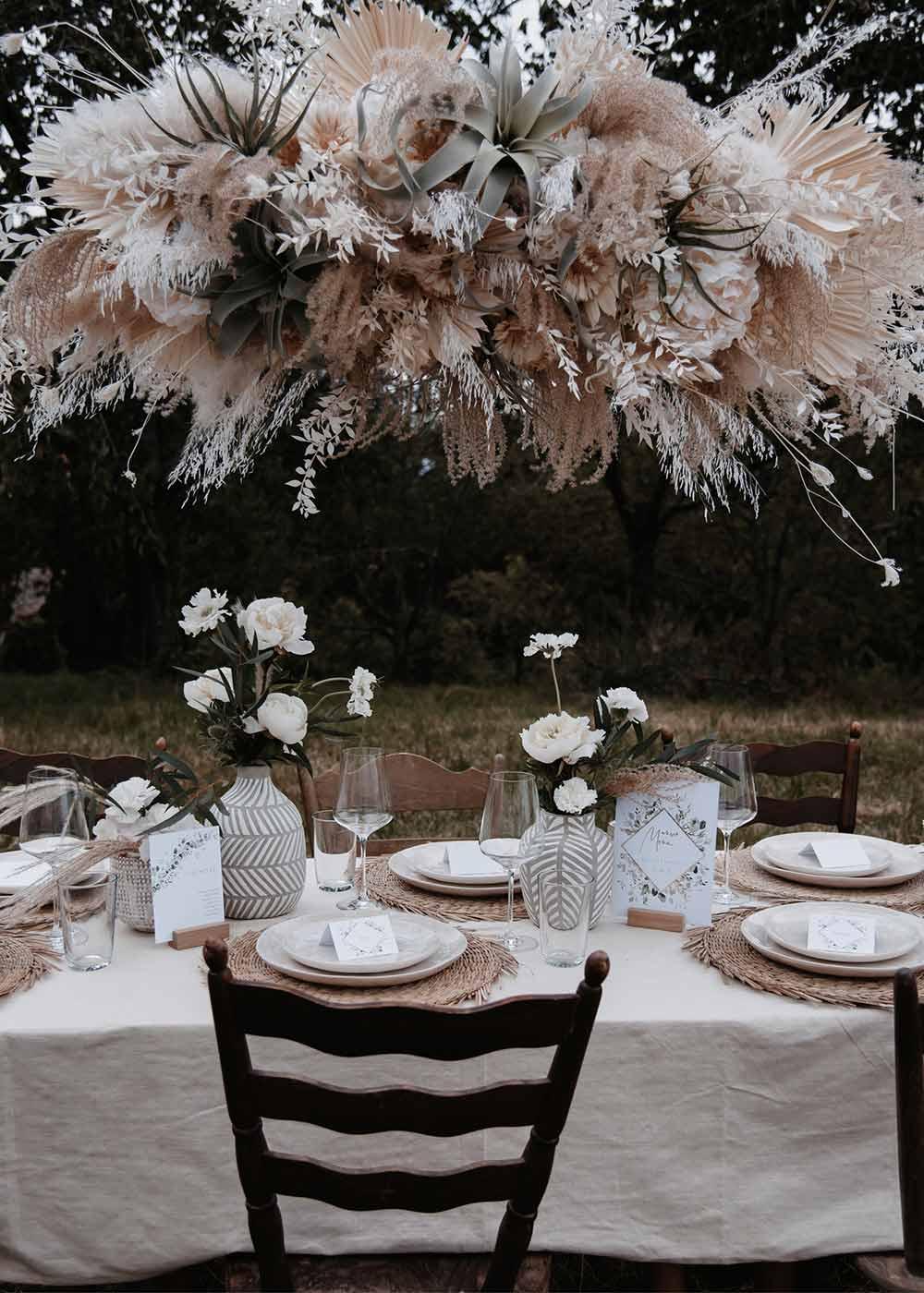 Das Highlight am Hochzeitstisch ist die auffällige Pflanzendeko über den Tischen. Zusammen mit den Blumen auf den Tischen und der liebevoll ausgewählten Papeterie wirken sie sehr harmonisch.