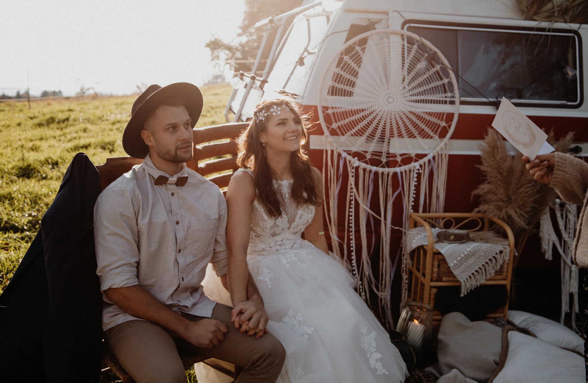 Verliebtes Brautpaar sitzt auf Holzstühlen und wird im Freien von einer Traurednerin getraut bei ihrer Picknick Hochzeit.
