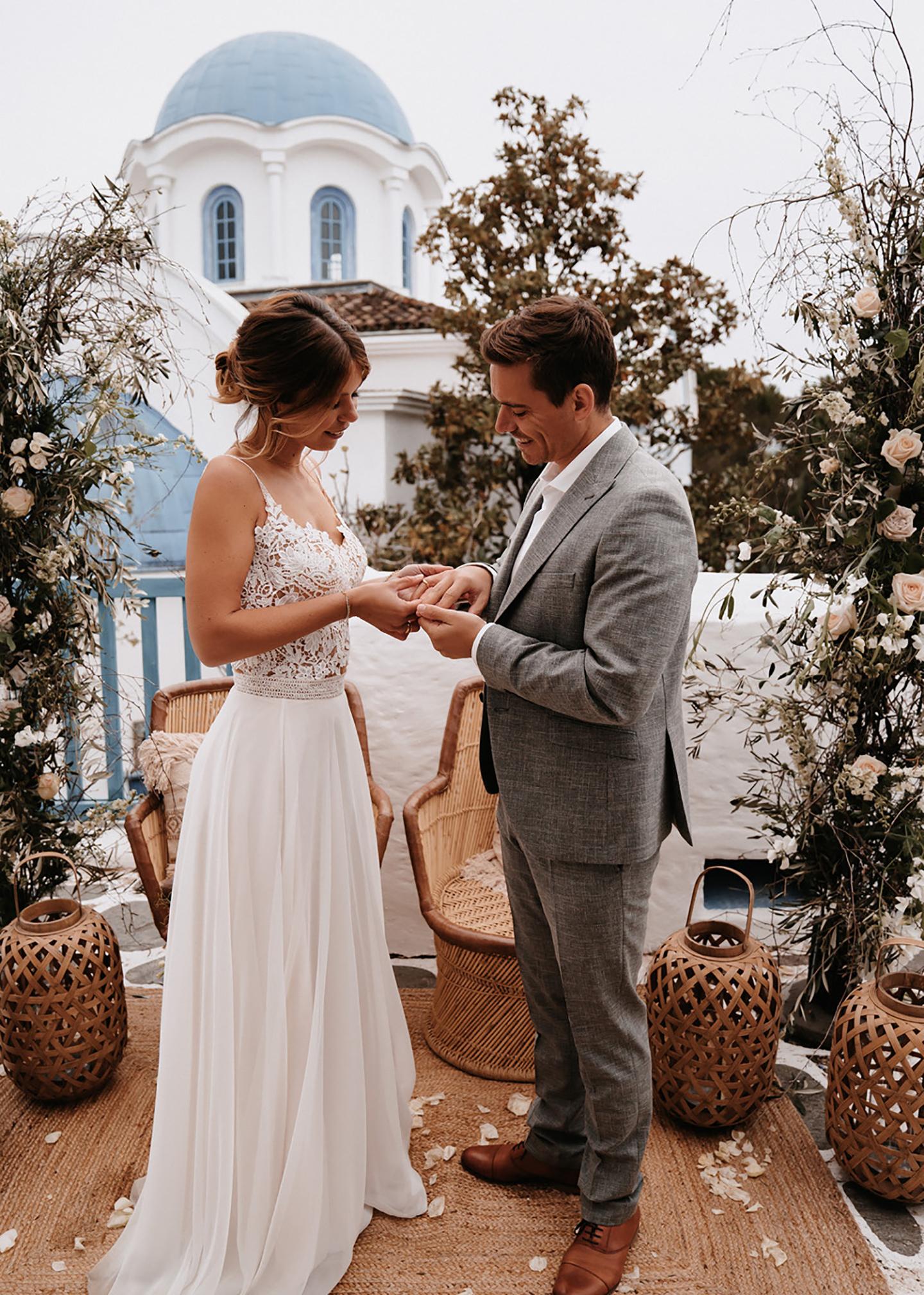 Vor dem Anblick einer griechischen Kapelle mit blauem Dach und geschmückter Atmosphäre steckt die Braut dem Bräutigam den Ehering an den Finger.