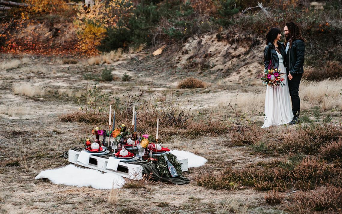 Das Hochzeitssetting befindet sich am Waldrand auf einer Lichtung, die einer alten Kiesgrube nahe kommt. Der gedeckte Hochzeitstisch ist in diesem Fall eine Holzpalette mit Deko und Kerzen, die für das Essen gedeckt wurde.
