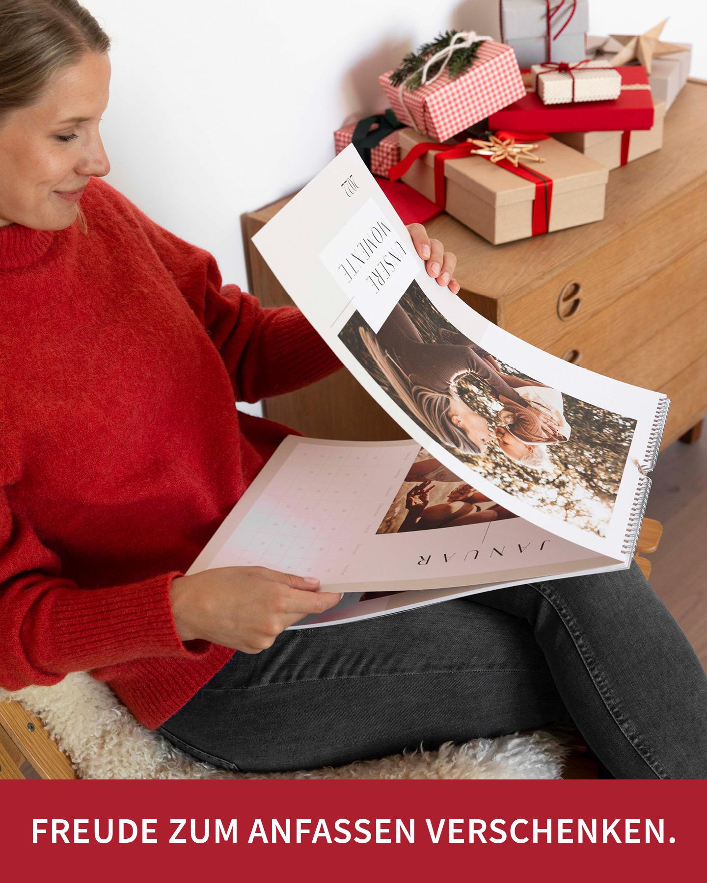 Frau im roten Pullover blättert durch Wandkalender mit vielen Familienfotos.