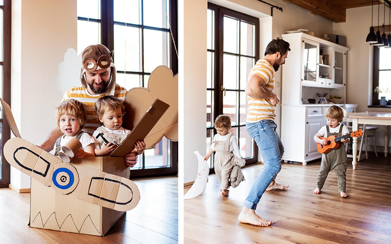 Ein Vater spielt mit seinen zwei kleinen Kindern im Haus. Die drei toben herum und sitzen in einem Karton, der als Flugzeug umfunktioniert wurde.