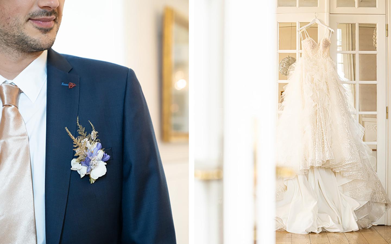 Der Bräutigam trägt einen dunkelblauen Anzug mit einer Beige-Peach Krawatte. Ein Ausschnitt davon ist zu sehen, ebenso wie. das pompöse und aufwändig verarbeitete Prinzessinnenkleid der Braut.