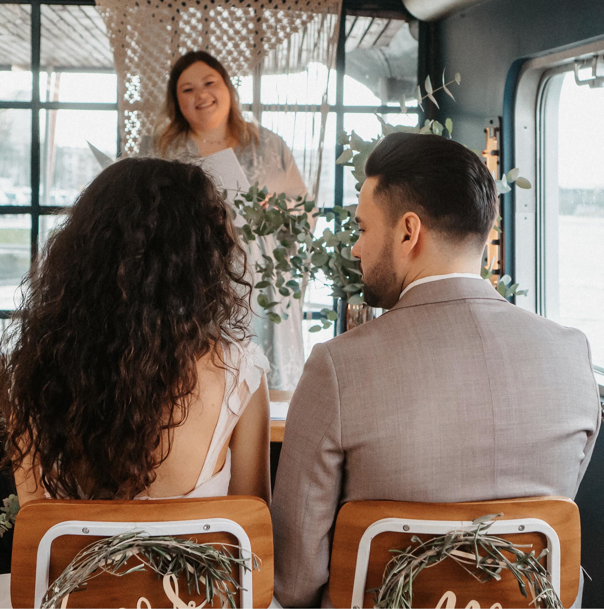 Brautpaar auf Schiff blickt freie Traurednerin an.