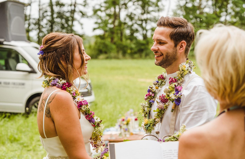 Hochzeitspaar hält sich bei der Camper Hochzeit an den Händen.