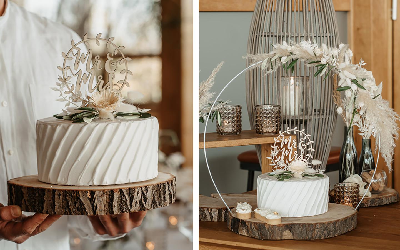 Die Hochzeitstorte wird auf einem Holzstück präsentiert, das aus einem Baumstamm geschnitten wurde. Die Torte ist schlicht weiß, in wellenartiger Form außen verziert und mit Pampasgras und Dekoelementen verziert.