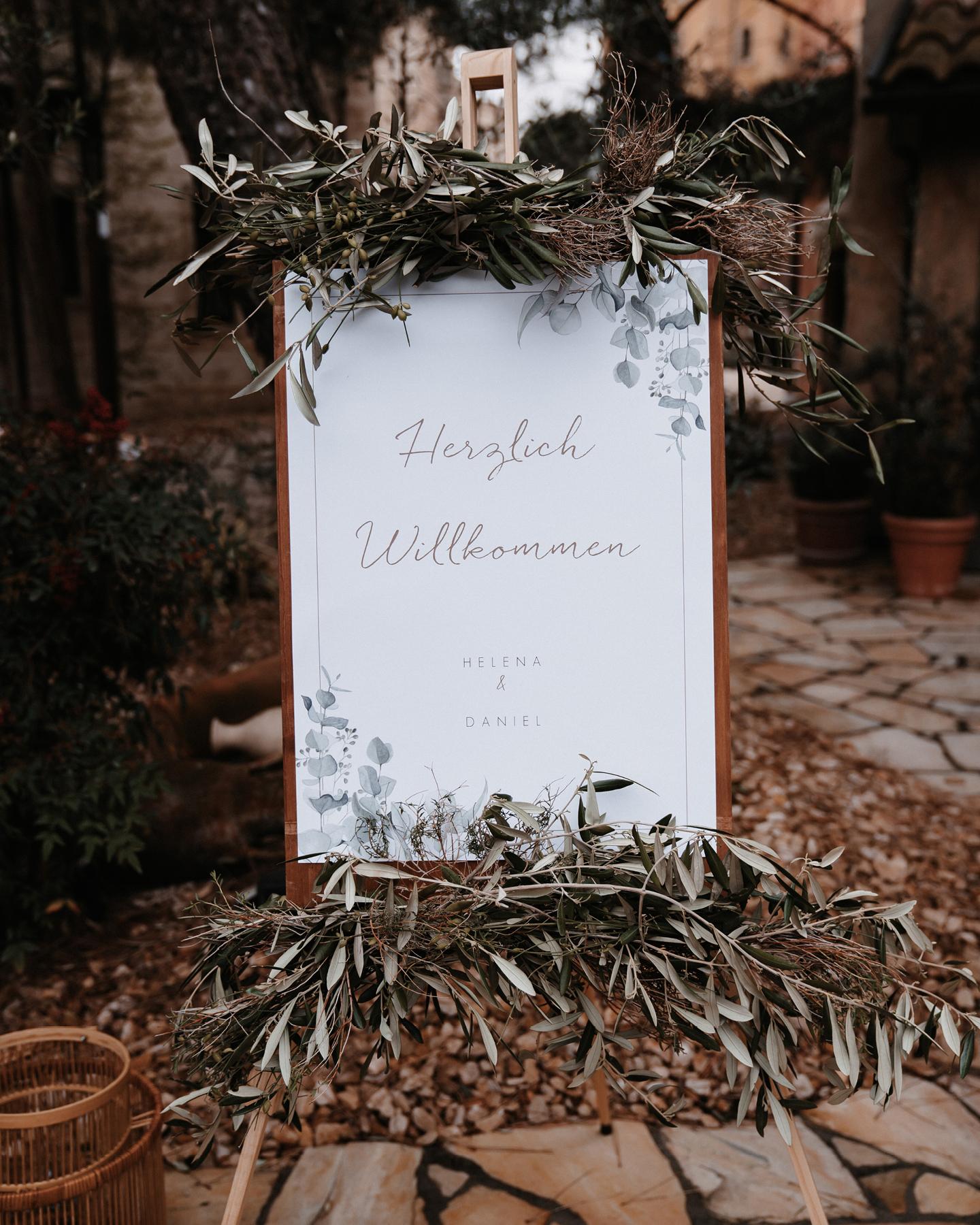 Willkommensschild mit Eukalyptus Illustration ist dekoriert auf einer Staffelei mit Olivenzweigen.