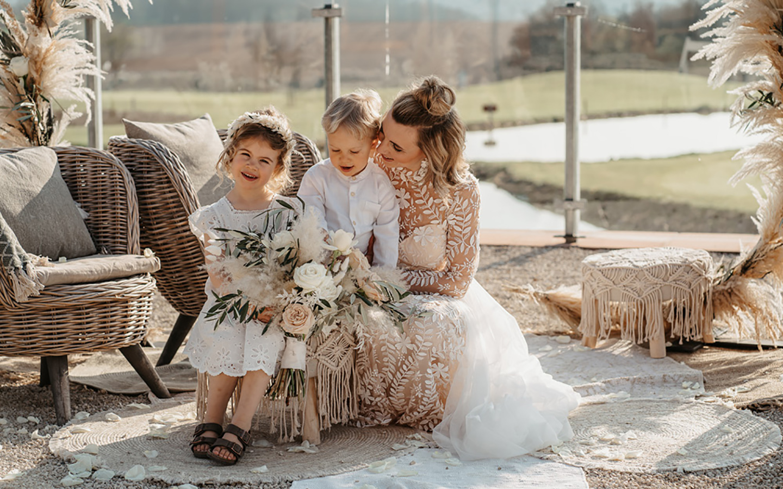 Die Braut und ihre zwei kleinen Kinder sitzen im Freien in der Sonne unterhalb des Traubogens, bereit für Fotos.