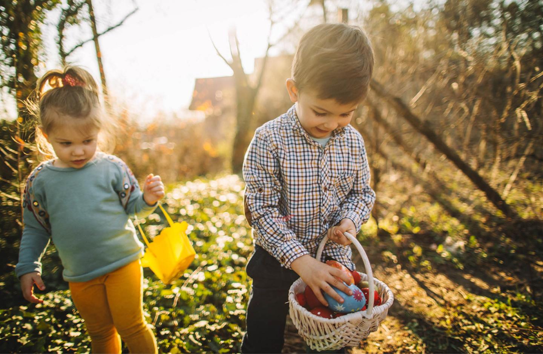 Ein Junge und ein Mädchen sind auf der Suche nach Ostereiern im Garten.