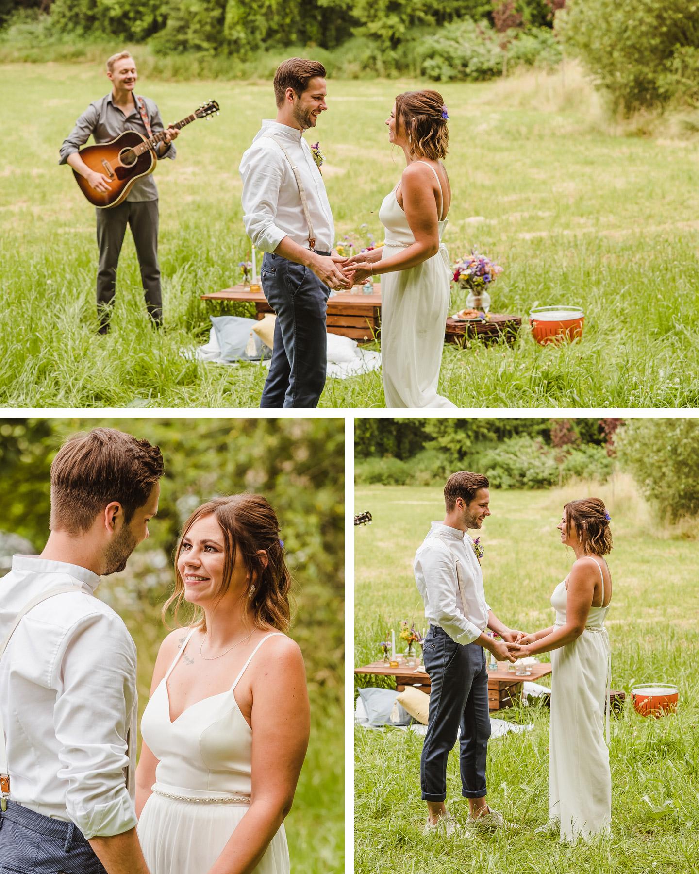 Brautpaar hält sich an den Händen und steht auf einer Wiese. Im Hintergrund spielt ein Mann Gitarre und ein Picknick ist aufgebaut.