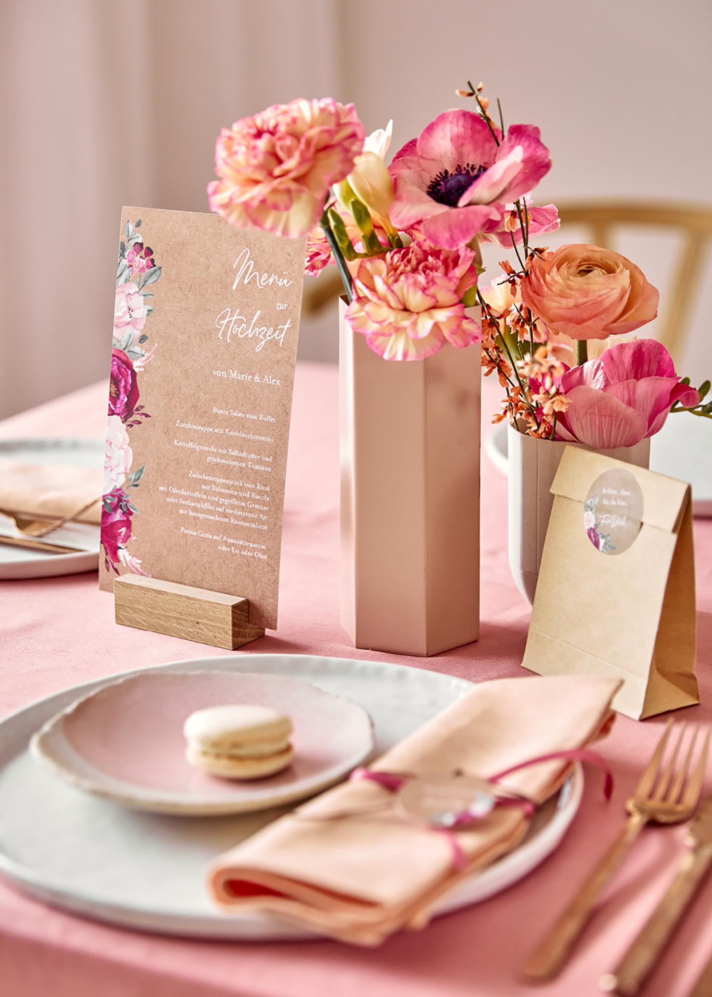 Tischpapeterie liebevoll dekoriert in soften und leuchtenden Pinktönen. Die Blumen auf dem Tisch passen farblich zur Tischdeko und ein Maccaron schmückt den gedeckten Teller.