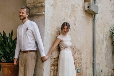 Hochzeitspaar an einer Mauer stehend umgeben von einem mediterrane Flair.
