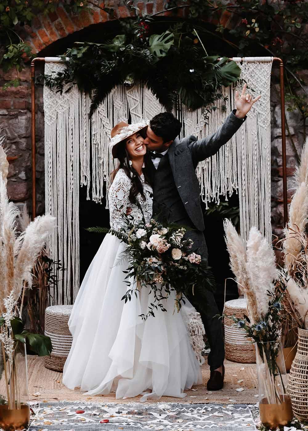 Das Brautpaar ist nach der Trauung glücklich und posiert vor dem aufwendig geschmückten Hintergrund der Traulocation.