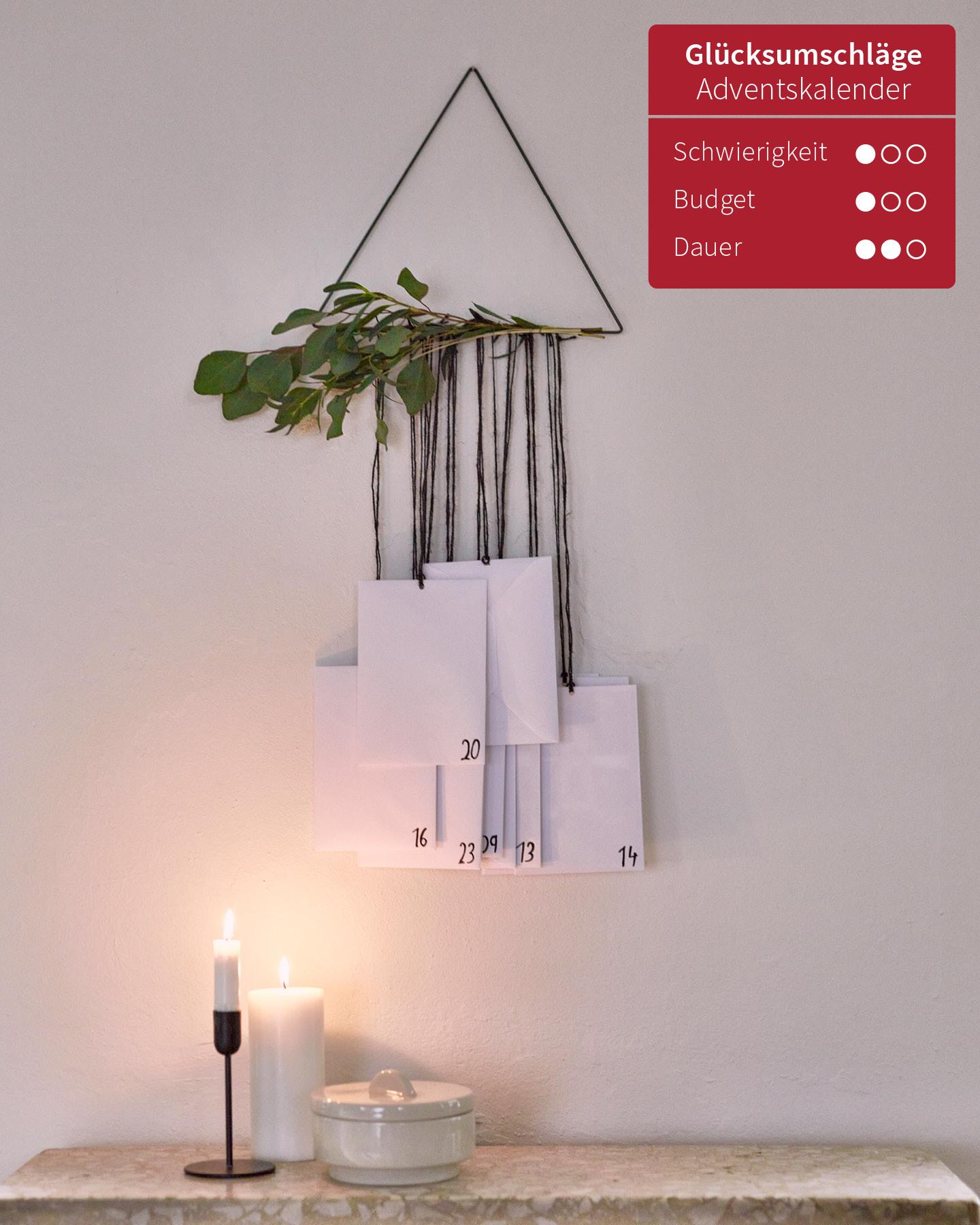 Selbstgemachter Adventskalender mit Umschlägen, die an einem Metalldreieck befestigt sind, hängt als Dekoelement an einer weißen Wand.