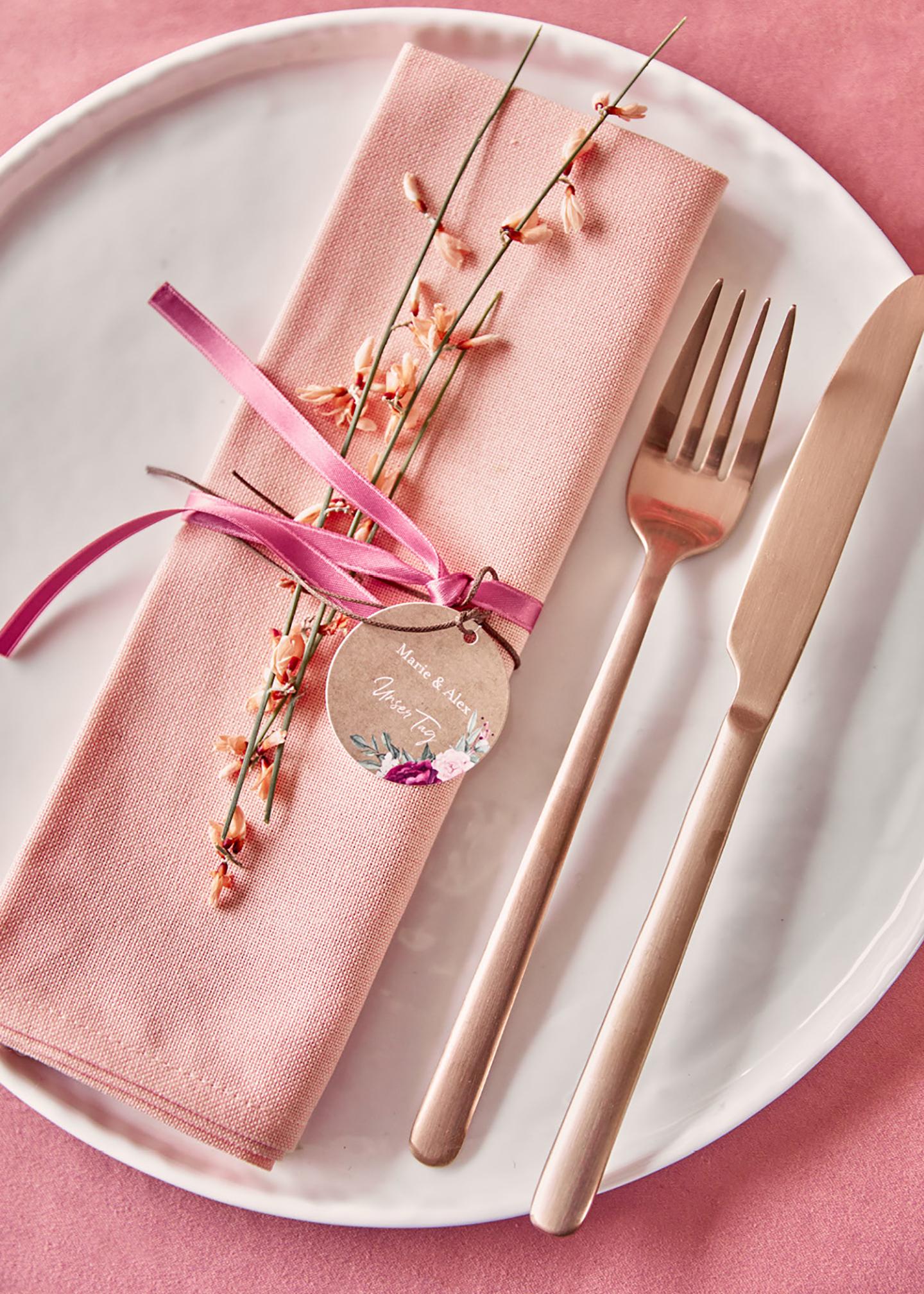 Besteck in Roségold liegt liebevoll drapiert auf dem gedeckten Teller. Die pinke Tischdeko passt wunderbar zur Serviette und der Schleife darum. Ein kleiner Zweig und ein Geschenkanhänger runden das Bild ab.