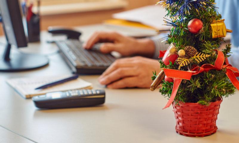 Am Schreibtisch sitzend vor dem Computer befindet sich ein Mitarbeiter eines Unternehmens. Sein Tisch ist geschmückt mit weihnachtlichen Accessoires. Zu dieser Zeit machen sich viele Unternehmer Gedanken, wie sie trotz DSGVO Weihnachtskarten verschicken