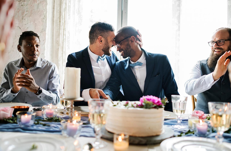Verliebtes Paar lacht glücklich an der Hochzeitstafel.