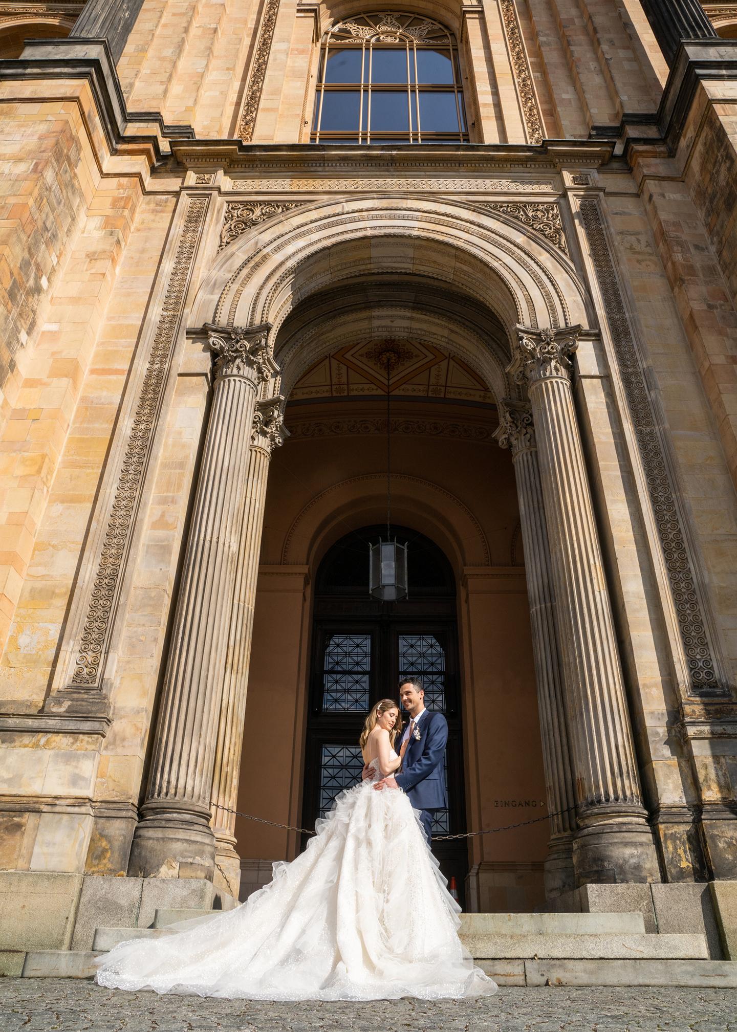 Das Hochzeitspaar bestehend aus Braut und Bräutigam steht vor einer beeindruckenden Architektur, in der die Trauung stattfindet. Vor der imposanten Tür posieren sie für Fotos.