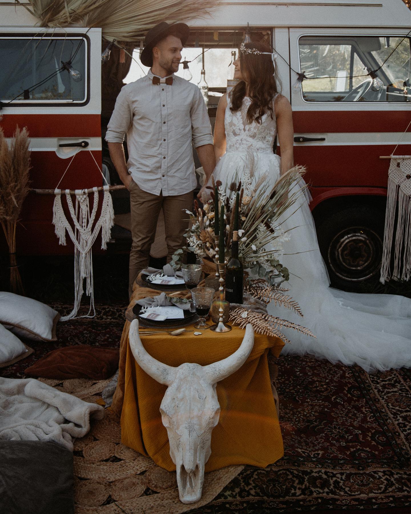 Verliebtes Boho Brautpaar feiert im Picknick Hochzeit. Als Dekoration werden ein Bulli, Pampasgras und Makramee-Elemente verwendet.