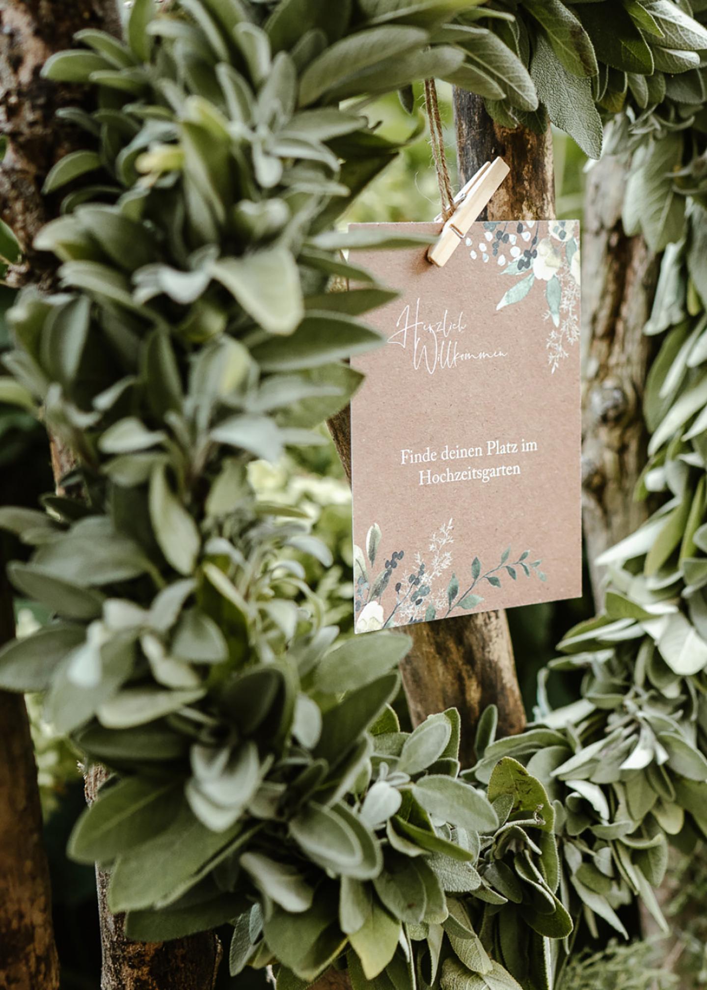 Ein grüner Kranz aus Blättern wird mittig von dem Willkommensschild geziert.