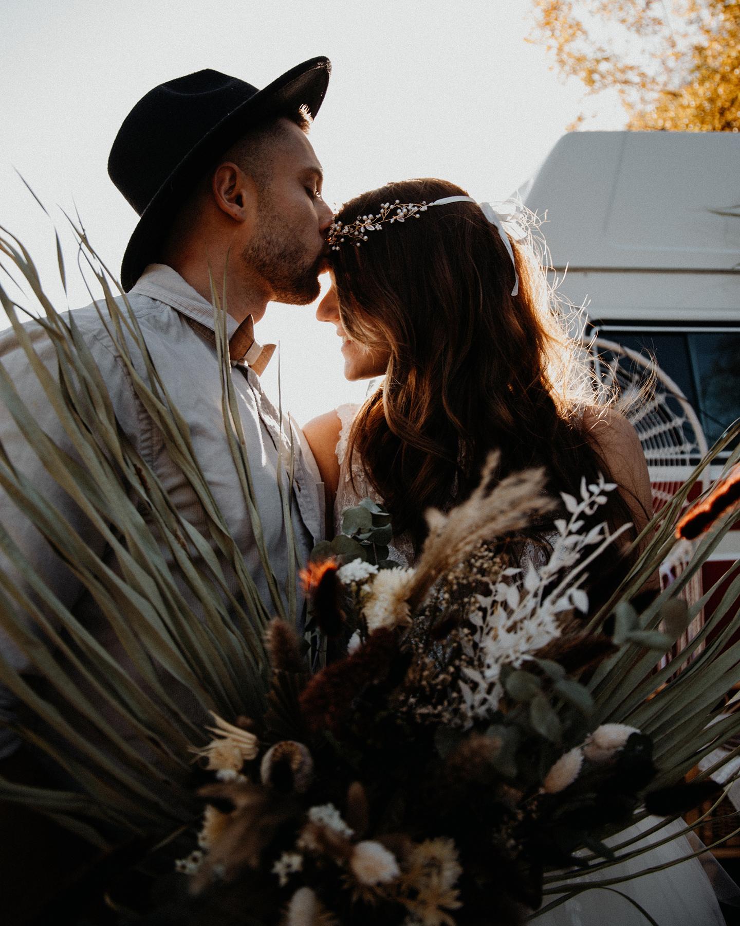Bräutigam küsst seine Braut im Boho Look auf die Stirn.