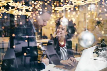 Zwei Mitarbeiter eines Unternehmens sind am Laptop zu sehen. Die Umgebung ist geschmückt mit weihnachtlicher Deko. Thema ist, wie unter Beachtung der DSGVO Weihnachtskarten geschrieben werden können