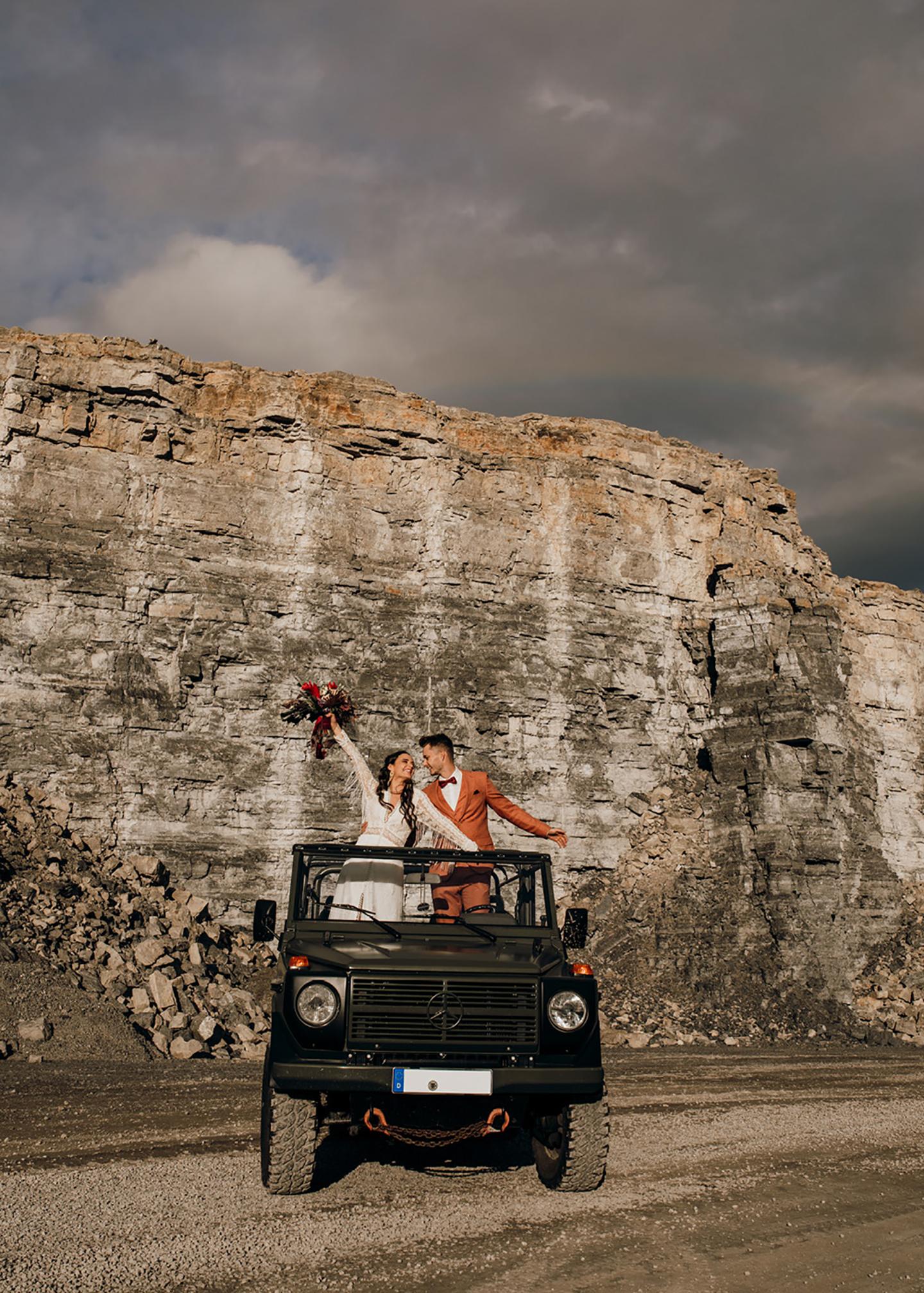 Die beeindruckende Kulisse des Shootings - ein Steinbruch, im Vordergrund das Brautpaar auf dem Geländewagen, dunkle Wolken und ein Regenbogen hinter ihnen
