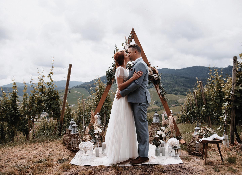 Brautpaar küsst sich zum Ja Wort vor Boho Traubogen und Deko aus Pampasgras: Checkliste zur Hochzeit.