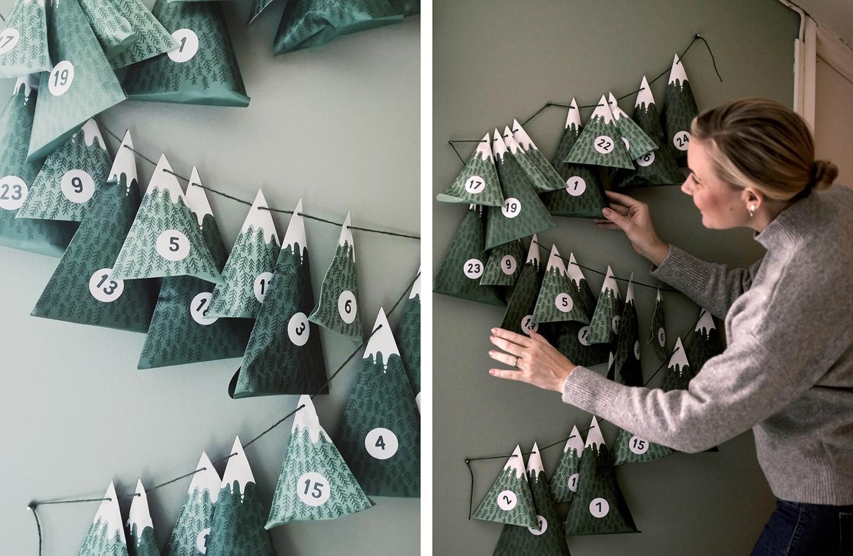 Frau freut sich über selbst gebaselten Adventskalender aus Papier in Tannenbaum-Optik.