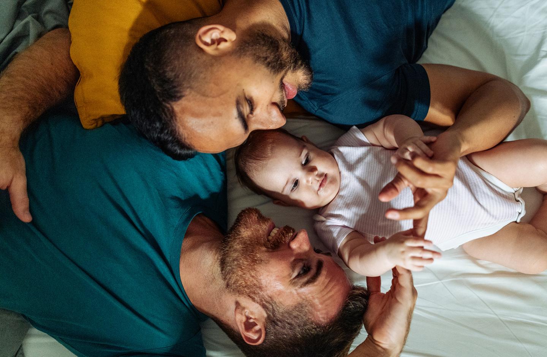 Zwei Papas kuscheln mit ihrem Baby auf dem Bett