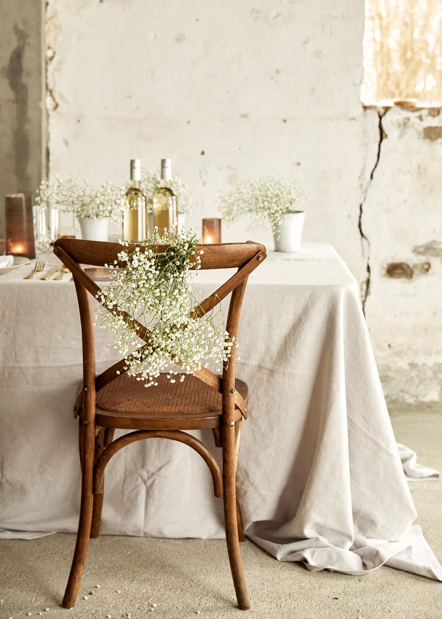 Tischdeko Hochzeit: Eine rustikale Location im Shabby-Chic-Look, ein im Vintage Stil dekorierter Hochzeitstisch mit weißer Tischdecke und dunklen Stühlen sowie goldenes Besteck und Schleierkraut geben ein harmonisches Bild.