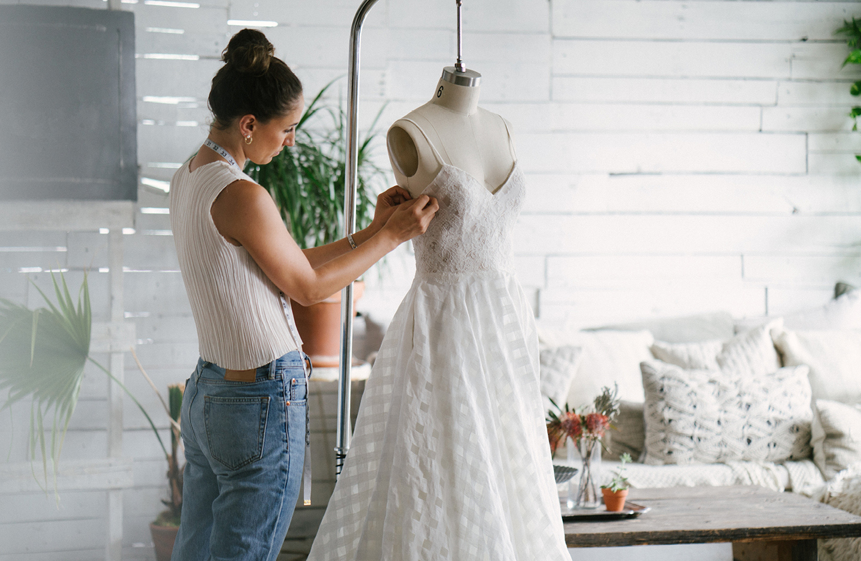 Schneiderin ändert Brautkleid an Schneiderbüste ab.